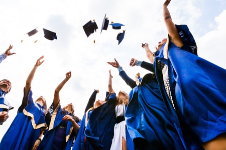 Image of happy young graduates throwing hats in the air