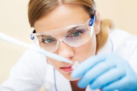 Foto de Young beautiful scientist working with samples in lab. - Imagen libre de derechos