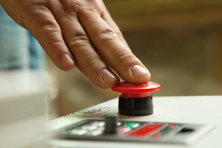 Photo pour Male hand pushing emergency red stop button. - image libre de droit