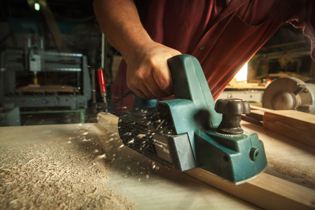 Photo pour Carpenter working with electric planer on wooden plank in workshop. - image libre de droit