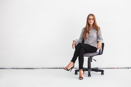 Photo pour Portrait of young beautiful business woman sitting on chair against white wall. - image libre de droit