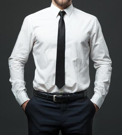 Foto de Midsection of fit young businessman standing in formal white shirt, black tie and pants. - Imagen libre de derechos