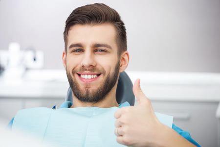 Photo pour My smile is perfect! Portrait of happy patient in dental chair. - image libre de droit