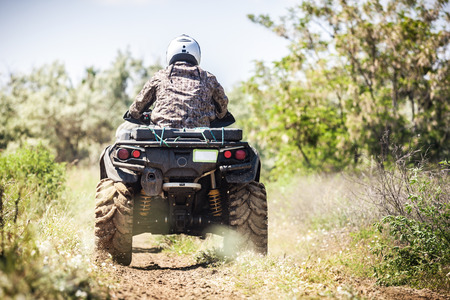 Photo for Back view of quad bike  zipping along a country road. - Royalty Free Image