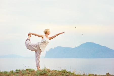 Photo pour Senior woman doing yoga exercises with mountain on the background - image libre de droit