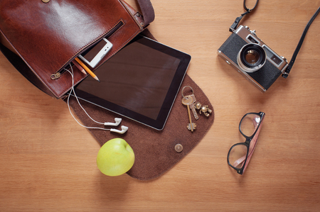 Foto de Outfit of traveler, student, teenager, young man. Overhead of essentials for modern young person. Different objects on wooden background: leather bag, camera, smartphone, glasses, keys, digital tablet - Imagen libre de derechos
