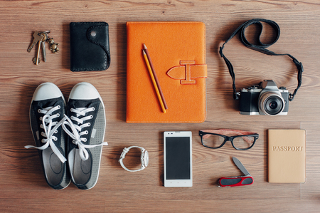Foto per Outfit of traveler, student, teenager, young woman or guy. Overhead of essentials for modern young person. Different photography objects on wooden background. Items include keys, camera, smart phone, glasses, passport, digital tablet, wallet, folder, watc - Immagine Royalty Free
