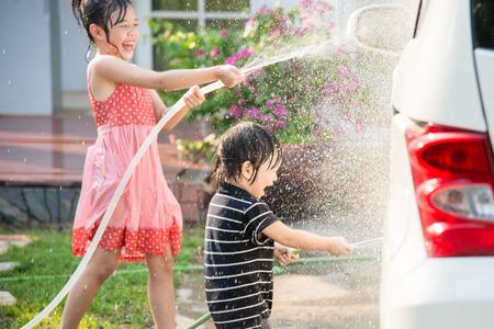 Foto per Asian children washing car in the garden - Immagine Royalty Free