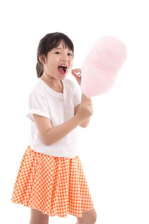 Foto de Cute asian girl holding pink cotton candy on white background isolated - Imagen libre de derechos