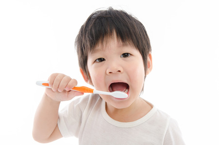 Photo pour Cute asian bay brushing teeth on white background isolated - image libre de droit