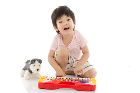 Little asian boy playing electrical toy piano on white background isolated