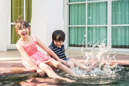 Foto de Asian children splashing around in the pool - Imagen libre de derechos