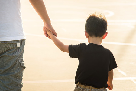 Foto de Father's hand lead his child son under sun light, trust family concept - Imagen libre de derechos