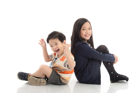 Photo for Two  happy asian children sitting and leaning on each other ,white background isolated - Royalty Free Image