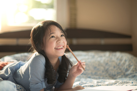 Photo for Beautiful asian girl thinking on the bed - Royalty Free Image