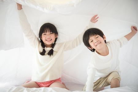Photo pour Cute asian children playing under blanket on white bed - image libre de droit