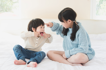 Photo pour Asian sister and brother quarreling on white bed - image libre de droit