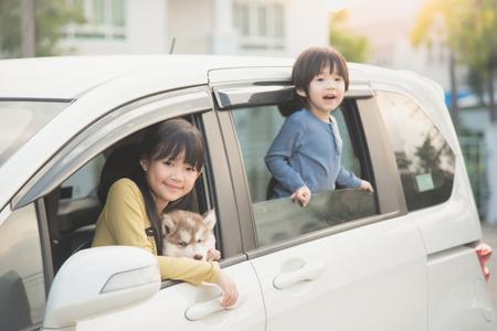 Photo pour Happy asian children and siberian husky puppy sitting in the car - image libre de droit