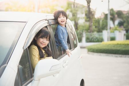 Photo pour Happy asian children sitting in the car - image libre de droit