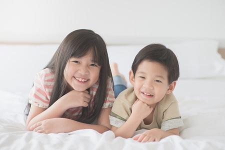 Photo pour Cute asian children lying on white bed - image libre de droit