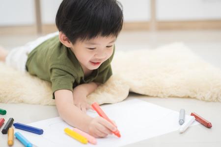 Foto de Cute Asian child drawing picture with crayon - Imagen libre de derechos