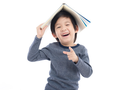 Photo pour Cute Asian boy with book on head thinking on white background isolated - image libre de droit