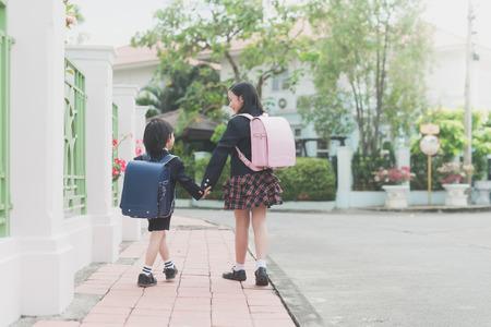 Foto de Cute Asian children  holding hand  together while  going to the school - Imagen libre de derechos