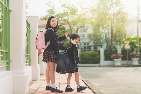 Photo for Asian students going to school and waving goodbye - Royalty Free Image