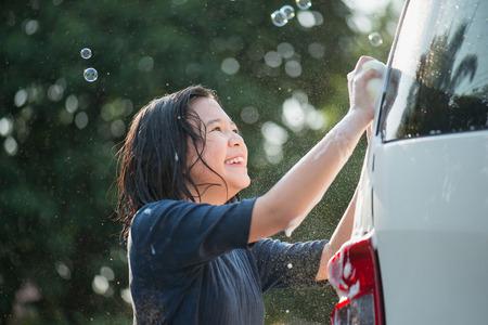 Photo pour Asian girl washing car in the garden on summer day - image libre de droit