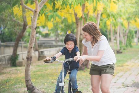 Foto de Beautiful and happy Asian mother teaching her cute son to ride a bicycle - Imagen libre de derechos