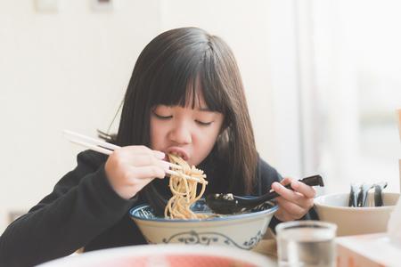 Foto de Beautiful Asian girl eating chashu ramen in japanese restaurant - Imagen libre de derechos