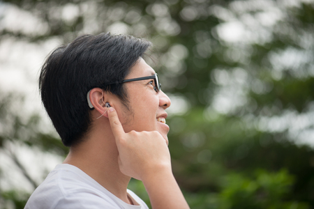Foto de Asian man with hearing aid behind the ear outdoors - Imagen libre de derechos