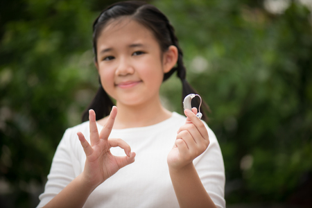 Foto de Beautiful asian girl holding hearing aid - Imagen libre de derechos