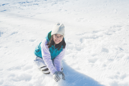 Photo for Happy asian girl smiling outdoors in snow on cold winter day - Royalty Free Image