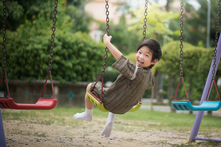 Foto de Cute Asian child in kimono playing on swing in the park - Imagen libre de derechos