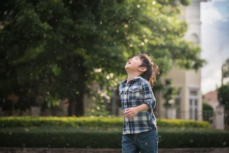 Photo pour Cute Asian child looking up in the park under the rain - image libre de droit