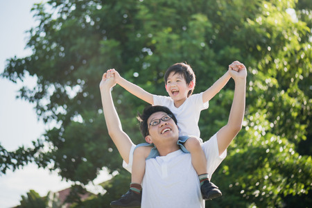 Photo pour Asian father and son playing in the park - image libre de droit
