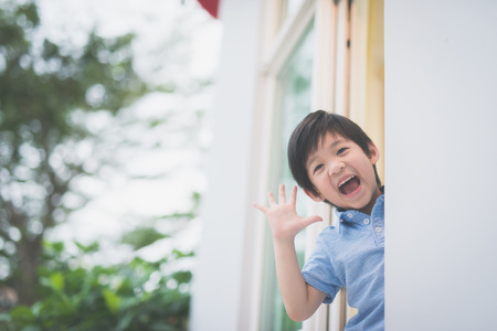 Photo for Portrait of cute Asian child at the open window - Royalty Free Image