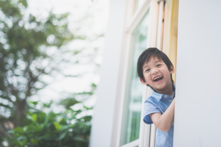 Foto de Portrait of cute Asian child at the open window - Imagen libre de derechos
