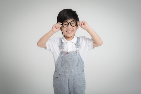 Photo pour Happy Asian child wearing glasses smiling on gray background - image libre de droit