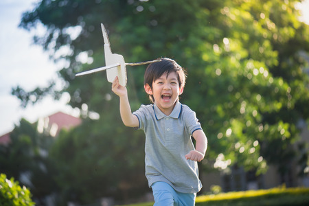 Foto de Cute Asian child playing cardboard airplane in thee park outdoors - Imagen libre de derechos