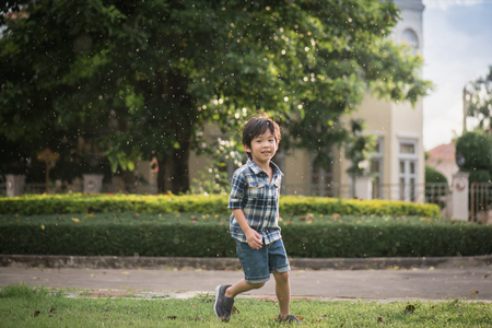 Foto de Cute Asian child playing in the park under the rain - Imagen libre de derechos