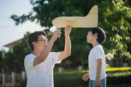 Photo for Asian father and son playing cardboard airplane together in the park outdoors - Royalty Free Image