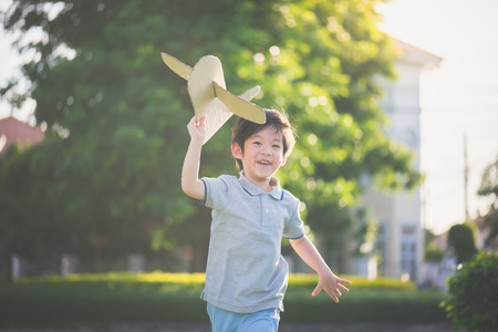 Photo for Cute Asian child playing cardboard airplane in thee park outdoors - Royalty Free Image
