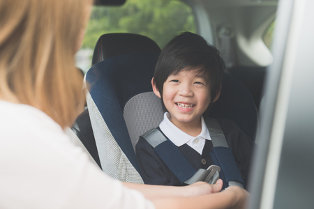Foto de Asian woman fastening child with safety seat belt in car - Imagen libre de derechos
