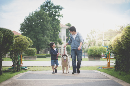 Foto de Asian father and son walking with a siberian husky don in the park - Imagen libre de derechos