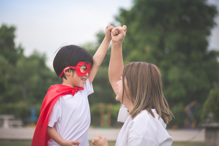 Photo pour Asian Mother and her son playing together in the park,Asian Mother and her son playing together in the park,Boy in Superhero's costume. - image libre de droit