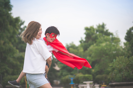 Foto de Asian Mother and her son playing together in the park,Boy in Superhero's costume. - Imagen libre de derechos