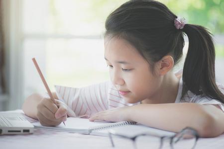 Foto de Beautiful asian girl writing to diary on the table - Imagen libre de derechos