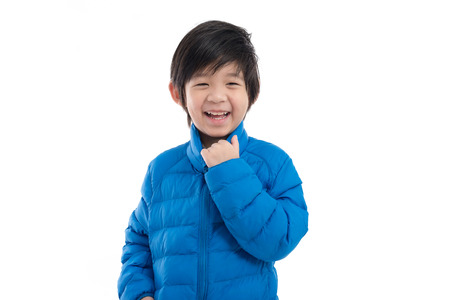Photo for Happy asian child in  blue winter clothes standing on white background isolated - Royalty Free Image